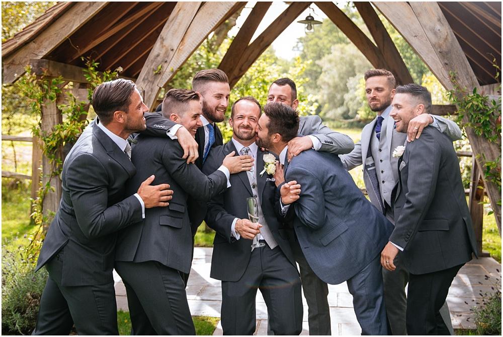 Groom being kissed by his friends