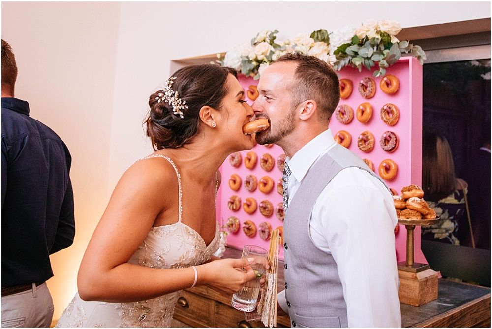 Bride and groom eat a donut from kalm kitchen donut wall
