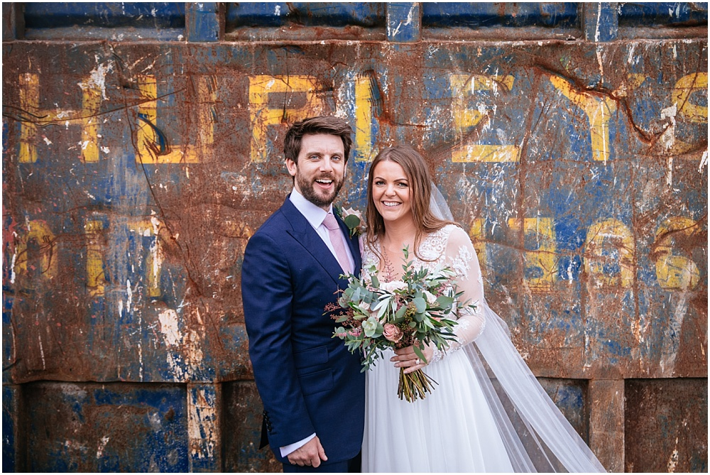 Bride and groom in front of cool skip