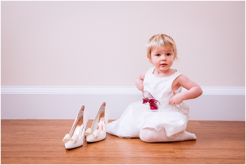 Flower girl plays with brides shoes