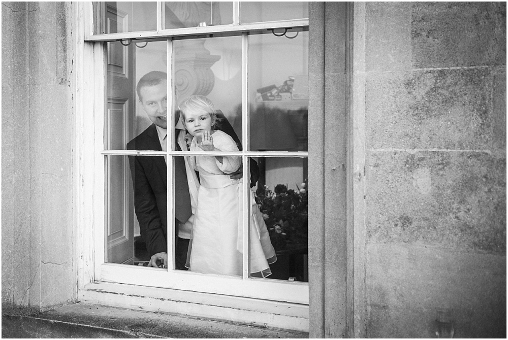 flower girl looks out of window at botleys mansion in surrey