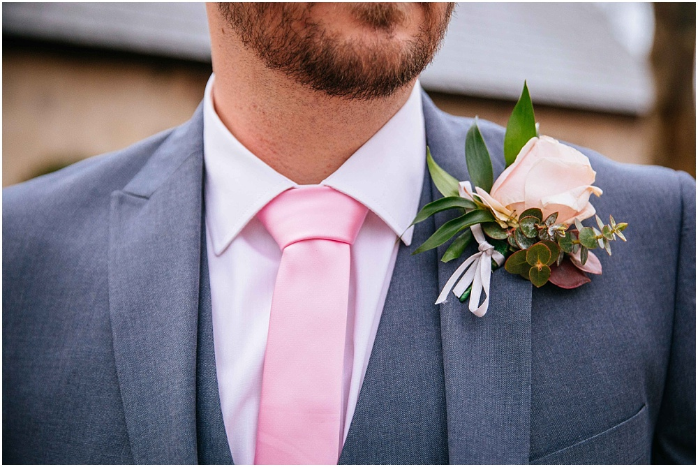 Groom with pink tie and rose button hole