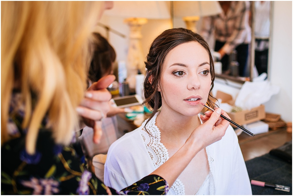 Applying lipstick to the bride
