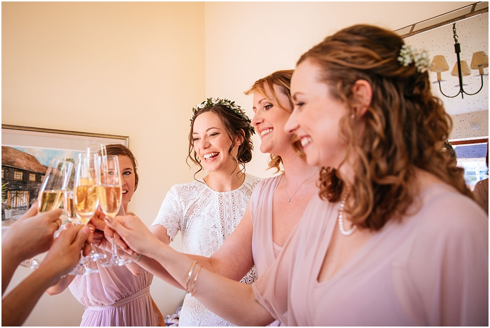 Cheers with bridesmaids pre wedding