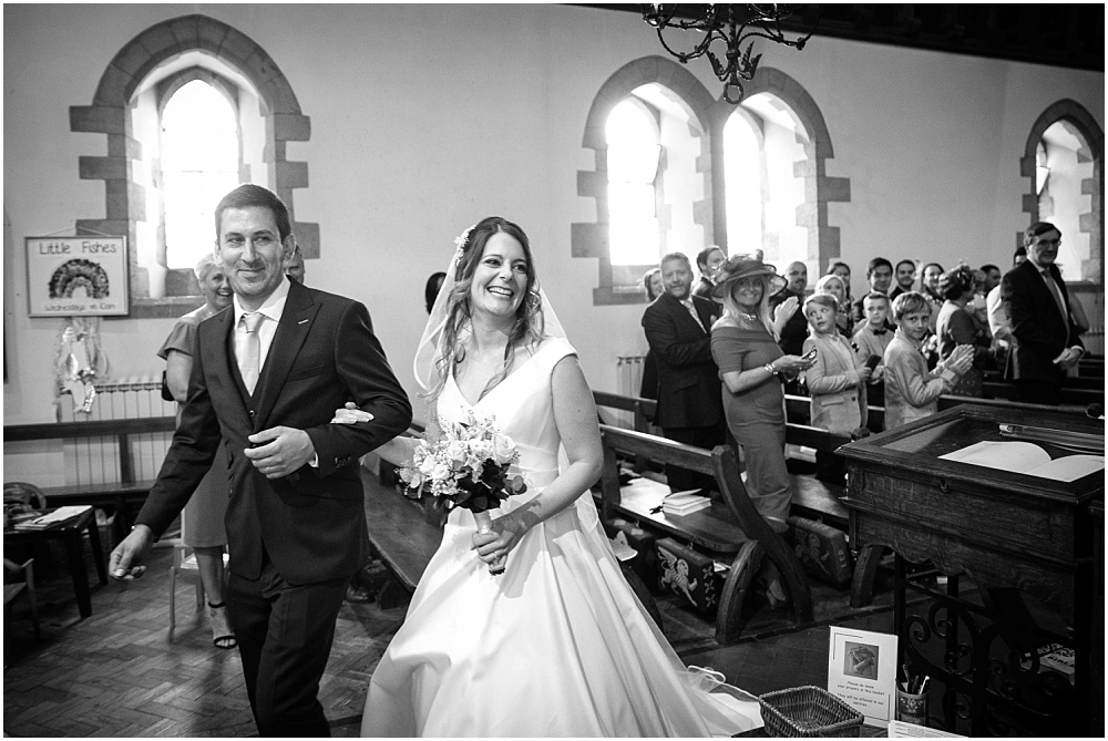Black and white photograph of bride and groom leaving church