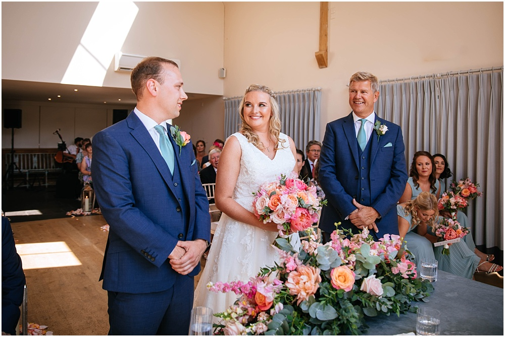 Bride grins at groom during wedding ceremony