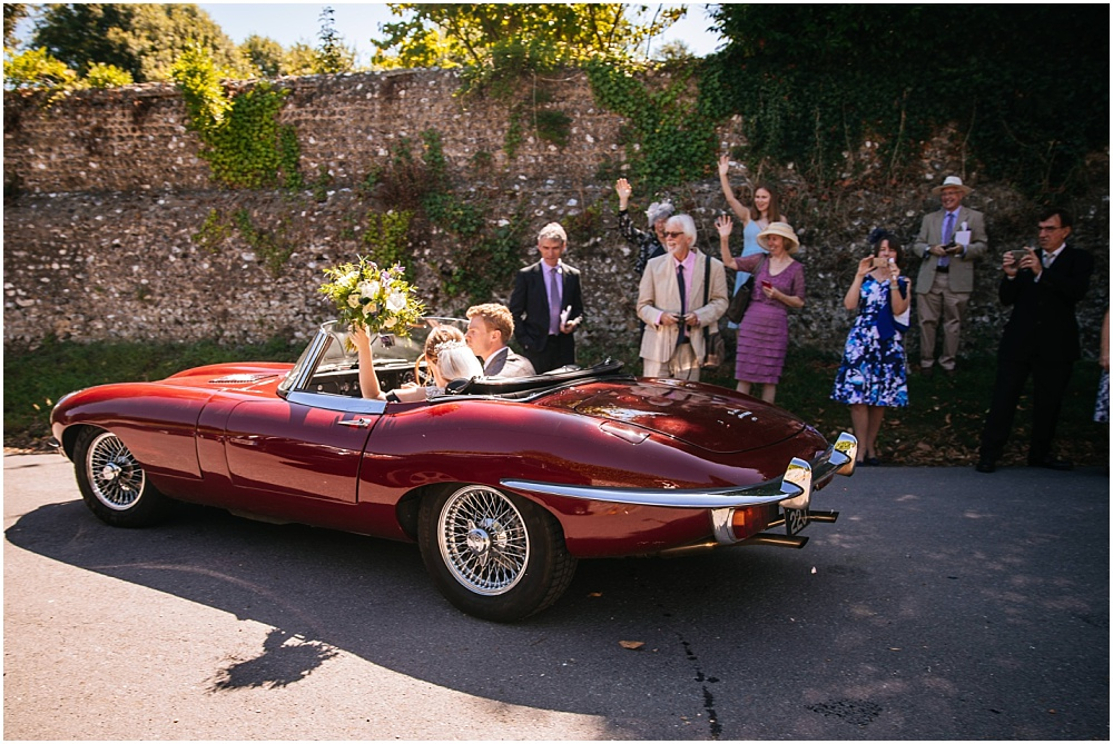 Bride and groom drive off in etype