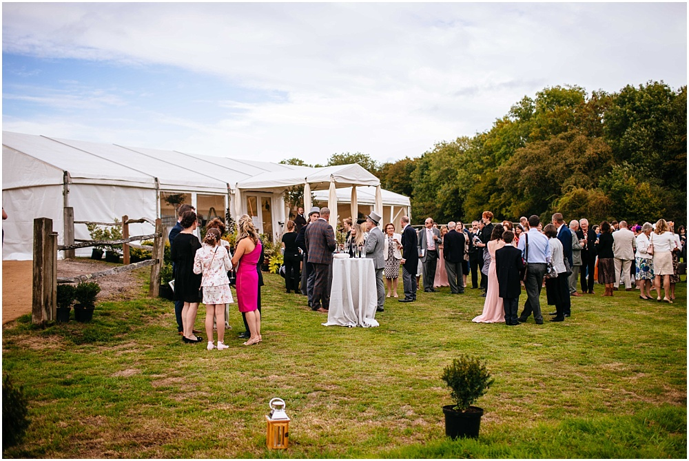 guests enjoy reception drinks outside marquee