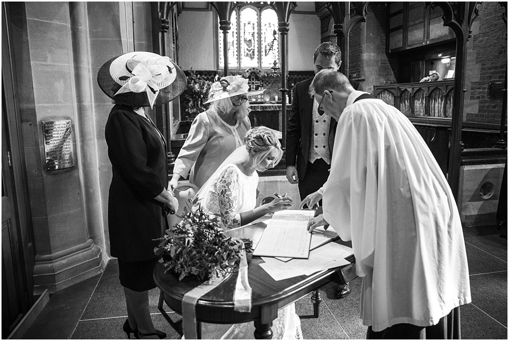 actually really signing the register in sunningdale church wedding