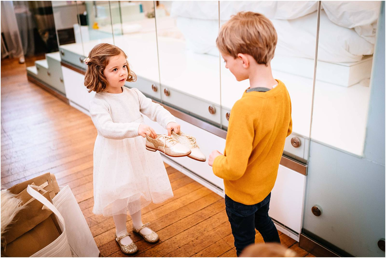 flower girl presents page boy with his gold next shoes