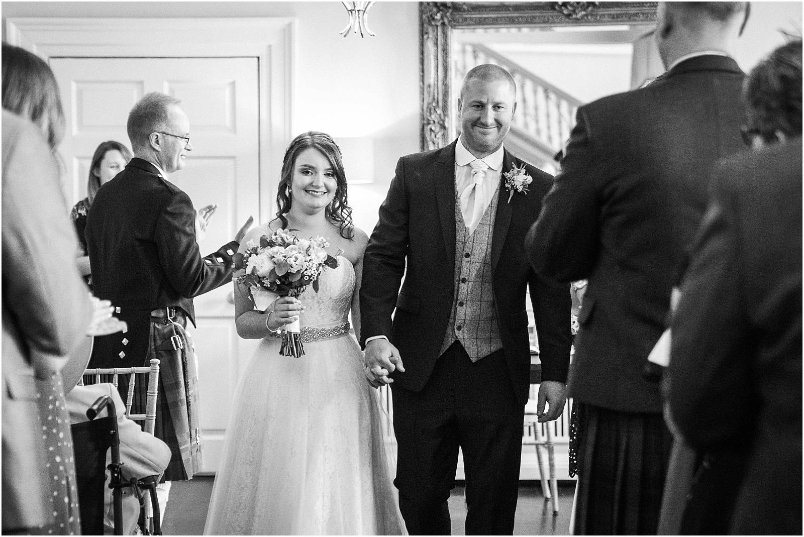 black and white photo of bride and groom walking back down the aisle