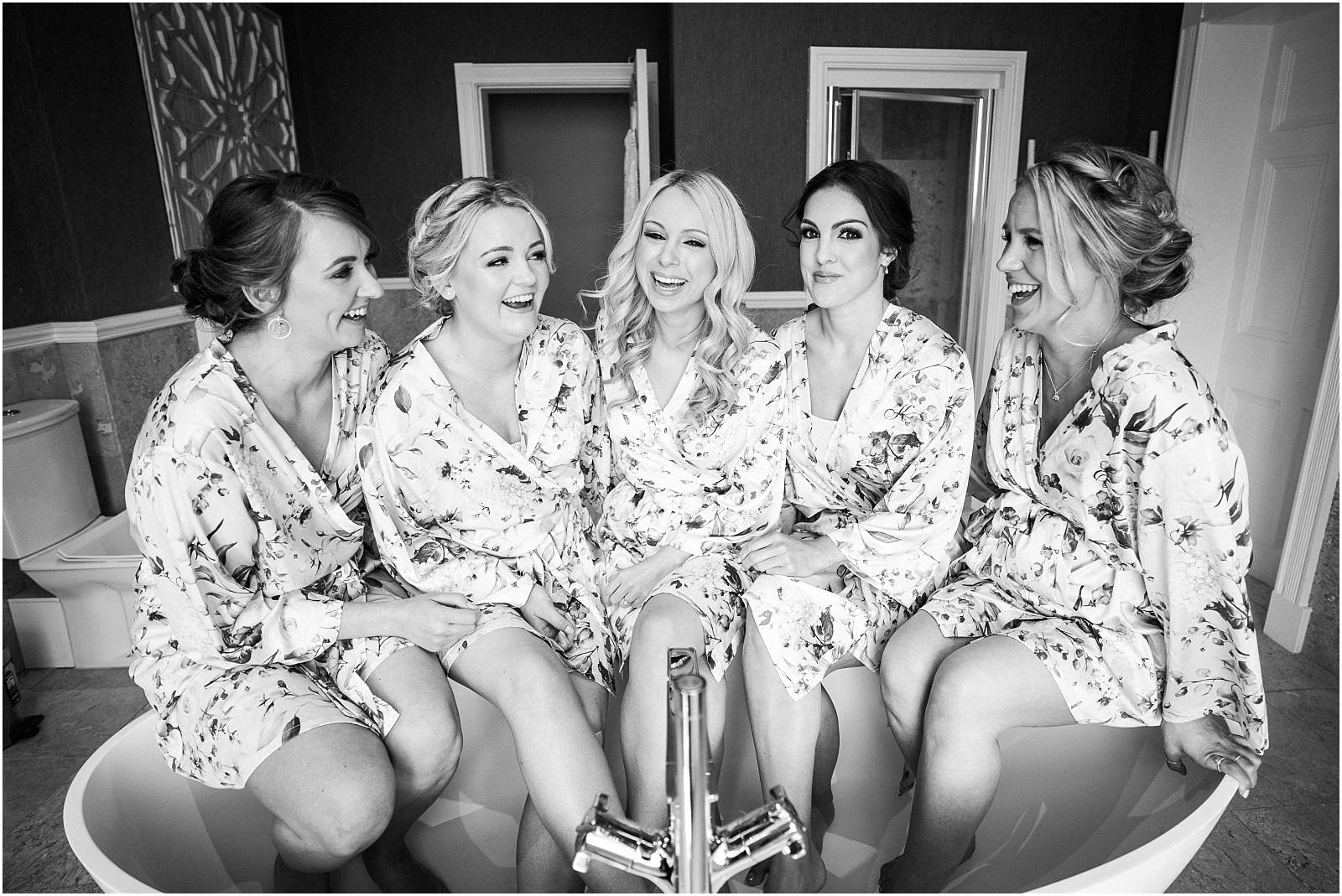 black and white photograph of bridesmaids sitting in bath together
