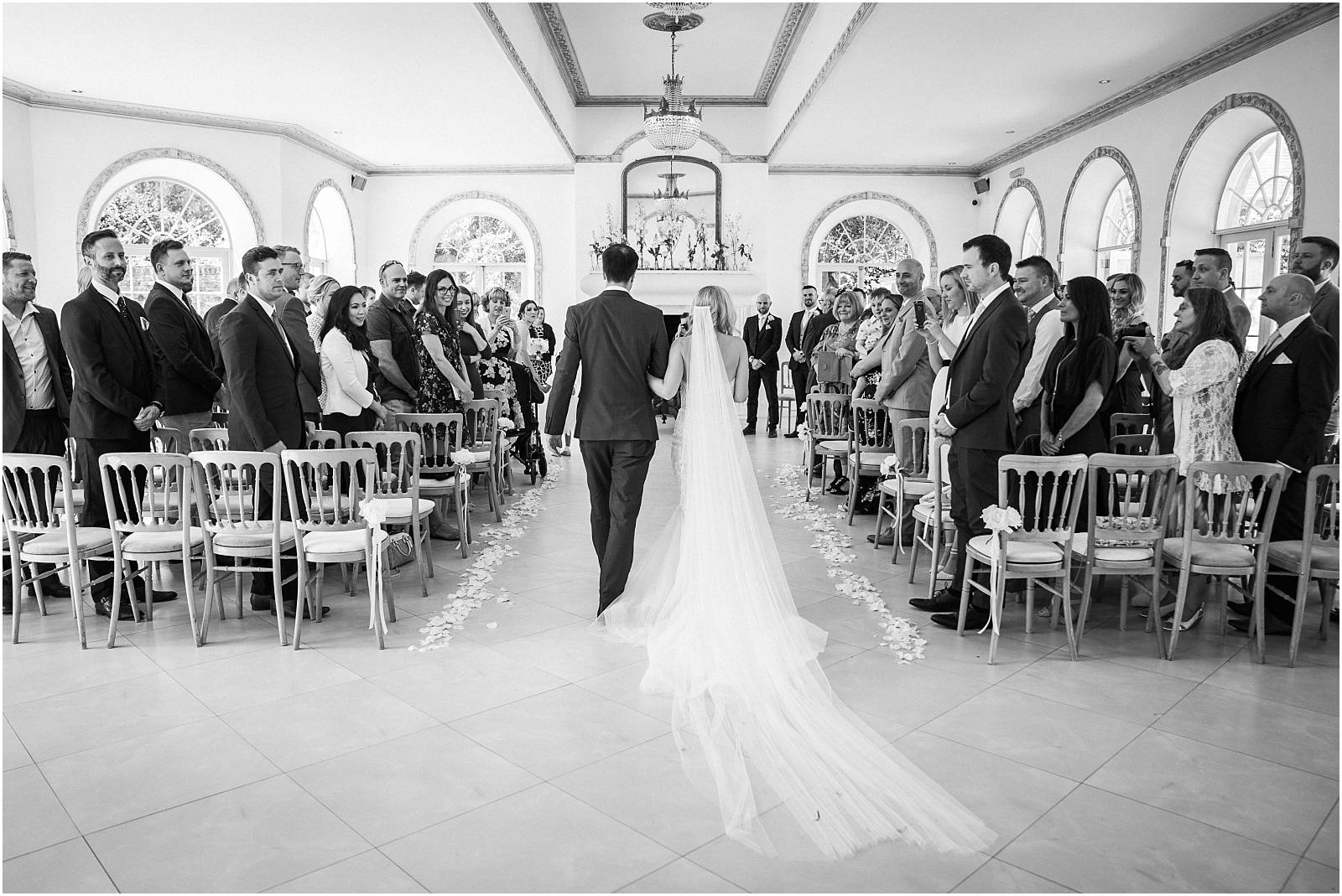 walking down the aisle in black and white from behind
