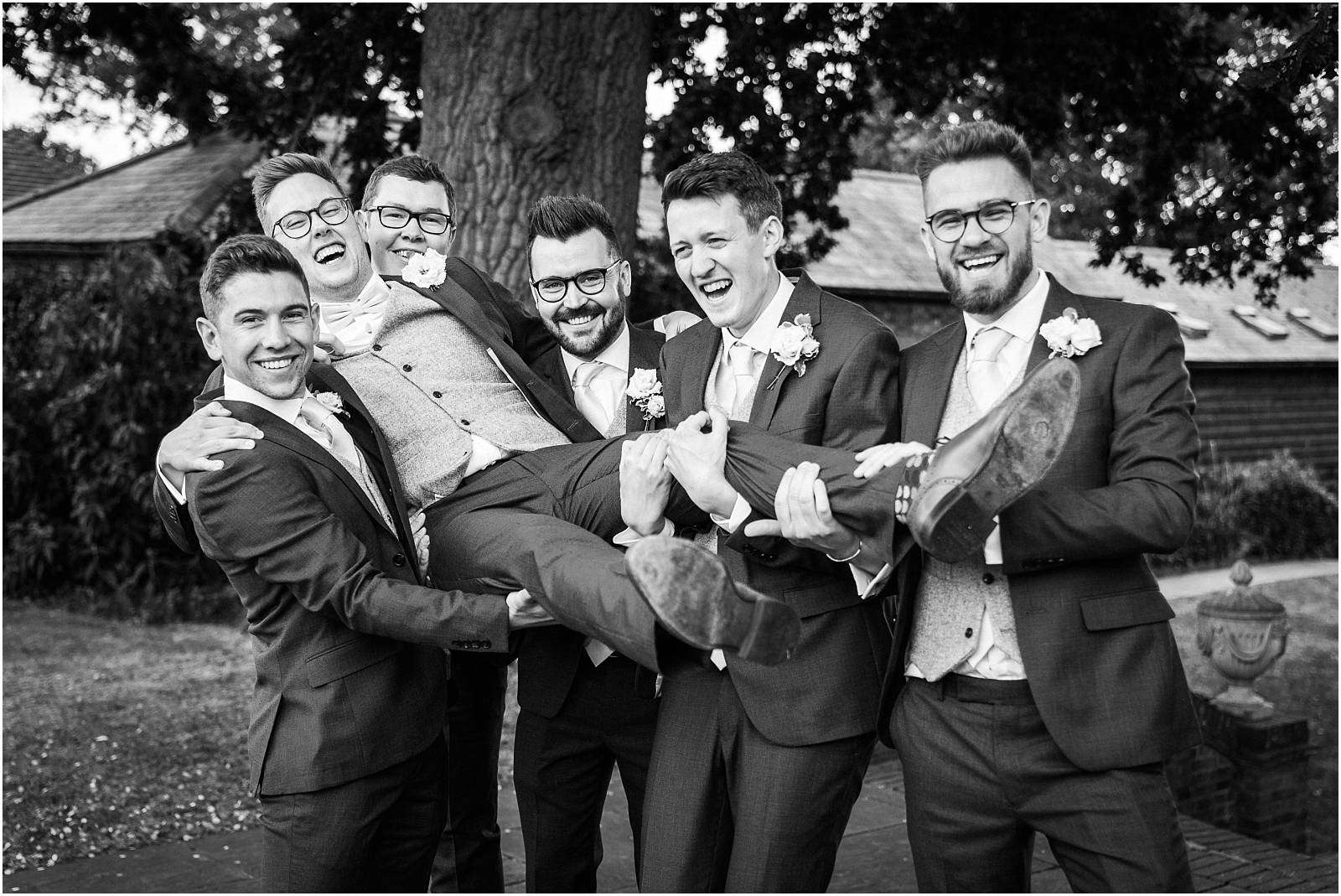 groom being lifted up by his groomsmen