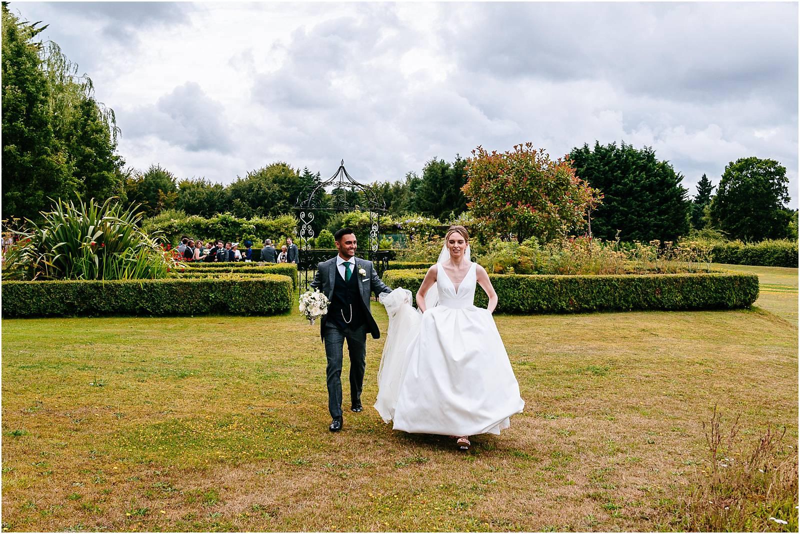 groom holding brides train