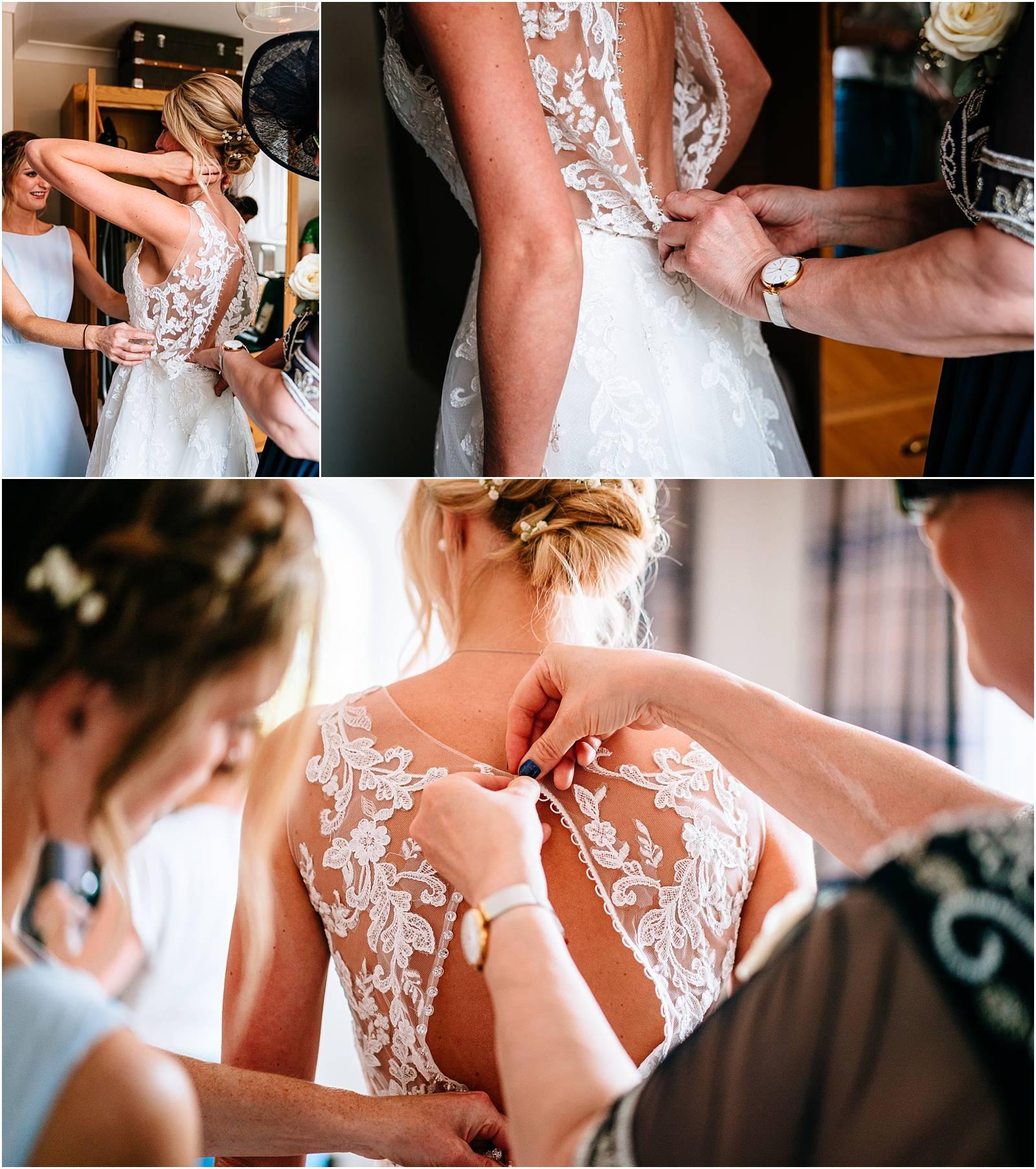 bride getting into stunning wedding dress