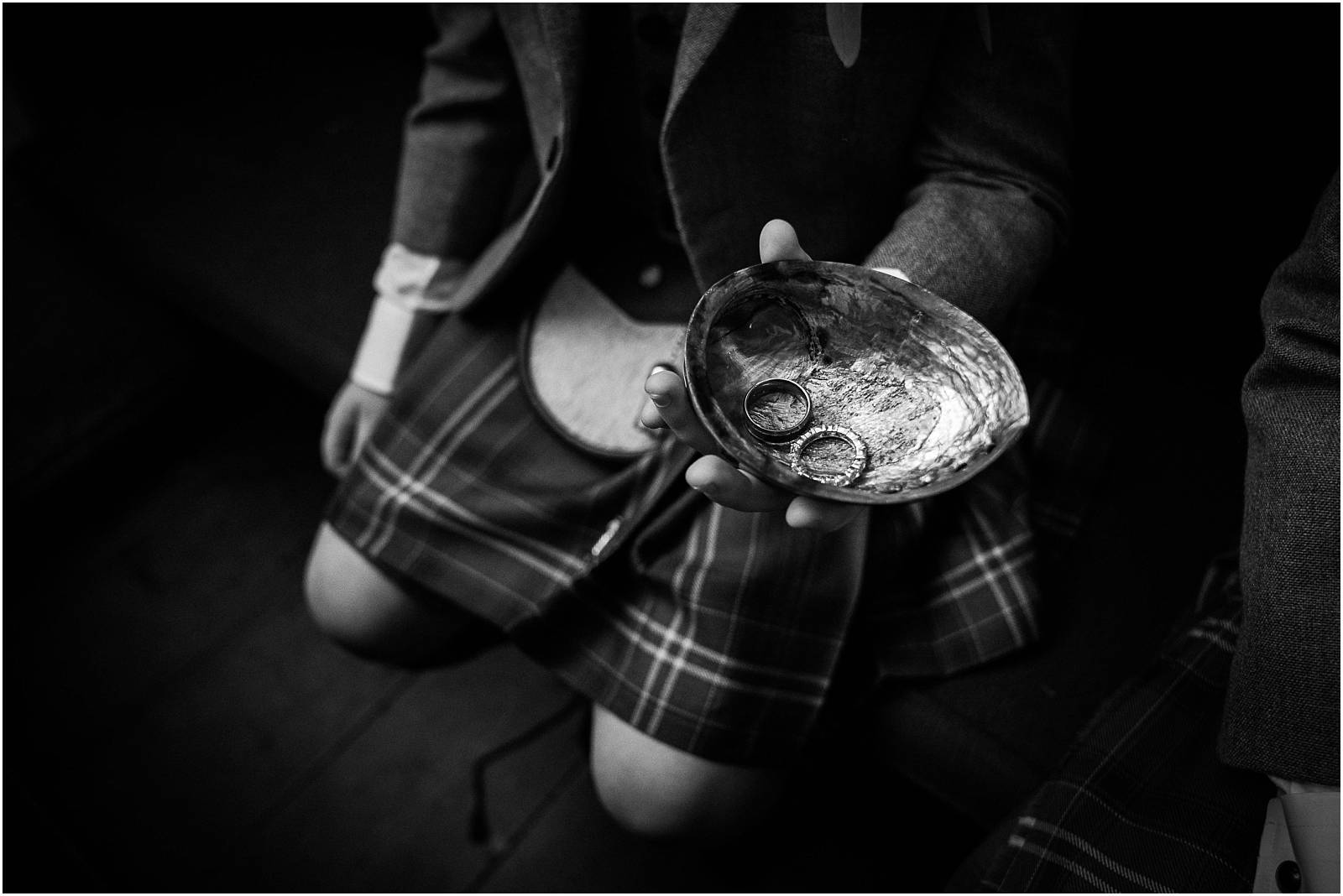 pageboy in kilt holds rings in shell